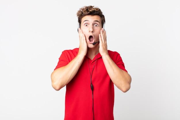 Młody przystojny mężczyzna czuje się zszokowany i przestraszony. koncepcja telemarketera