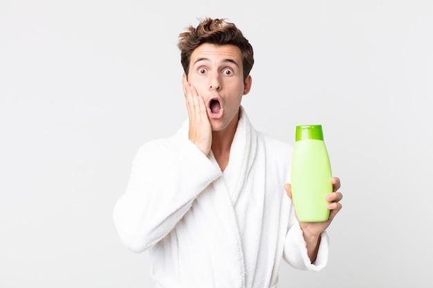 Młody przystojny mężczyzna czuje się zszokowany i przestraszony w szlafroku i trzyma butelkę szamponu