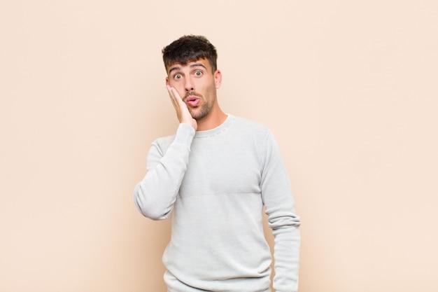 Młody przystojny mężczyzna czuje się zszokowany i zdziwiony, trzymając twarzą w rękę z niedowierzaniem z szeroko otwartymi ustami na ciepłej ścianie