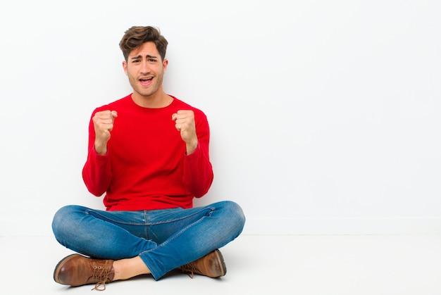 Młody przystojny mężczyzna czuje się zszokowany, podekscytowany i szczęśliwy, śmiejąc się i świętując sukces, mówiąc: wow! siedzenie na podłodze