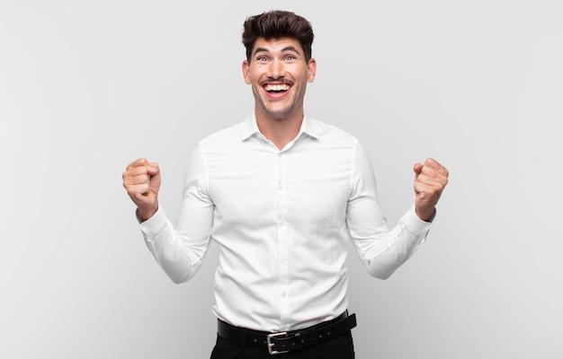 Młody przystojny mężczyzna czuje się zszokowany, podekscytowany i szczęśliwy, śmieje się i świętuje sukces, mówiąc wow!