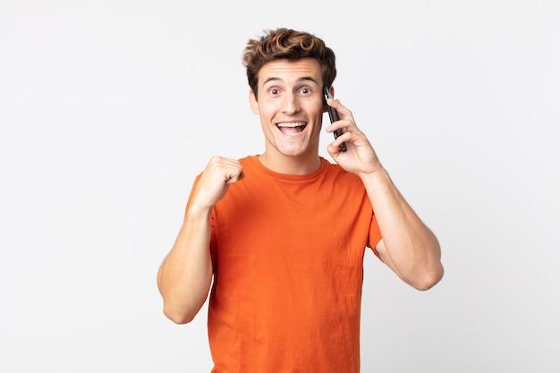 Młody przystojny mężczyzna czuje się zszokowany, śmieje się i świętuje sukces i rozmawia ze smartfonem