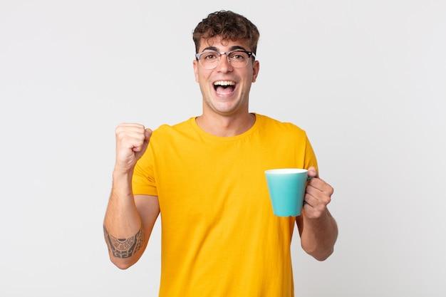 Młody przystojny mężczyzna czuje się zszokowany, śmieje się i świętuje sukces i trzyma filiżankę kawy