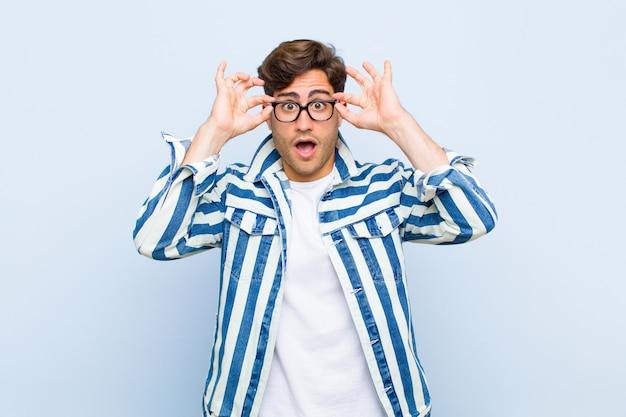 Młody przystojny mężczyzna czuje się zszokowany, zdumiony i zaskoczony, trzymając okulary o zdumionym, niedowierzającym spojrzeniu na niebieskiej ścianie