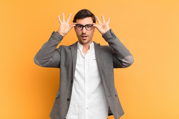 Młody przystojny mężczyzna czuje się zszokowany, zdziwiony i zaskoczony, trzymając okulary ze zdziwieniem i niedowierzaniem