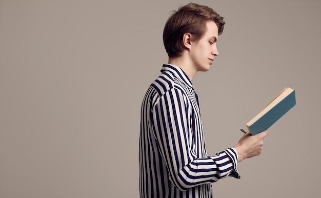 Młody przystojny mężczyzna czyta książkę na szarym tle w pasiastej koszula