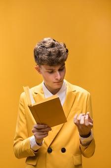 Młody przystojny mężczyzna czyta książkę w żółtej scenie