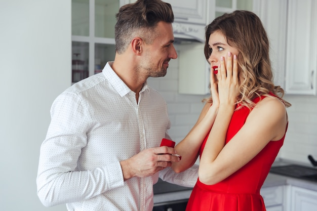 Młody przystojny mężczyzna daje pierścionkowi zaręczynowemu jego dziewczyna w domu