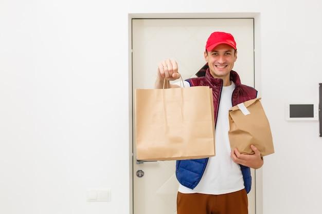 Młody przystojny mężczyzna dostarczający jedzenie w mieszkaniu