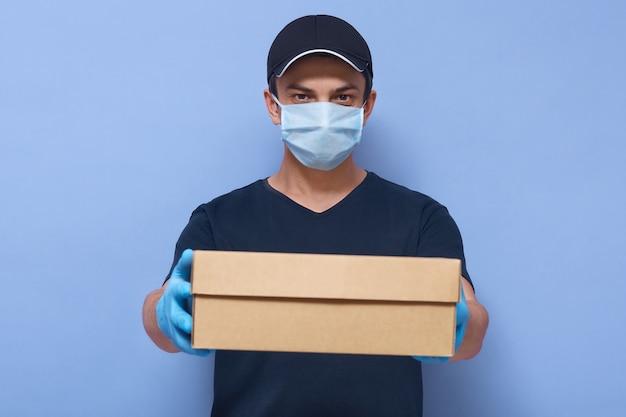 Młody przystojny mężczyzna dostarczający karton z ofertą dla klientów, kurier w koszulce, czapce, rękawiczkach lateksowych i medycznej masce na twarz, zapobiegający wirusom
