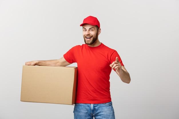 Młody przystojny mężczyzna dostawy trzymając karton i pokazując jego kciuk