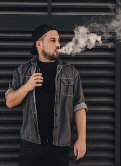 Młody przystojny mężczyzna dym z vape w pobliżu czarnej ściany