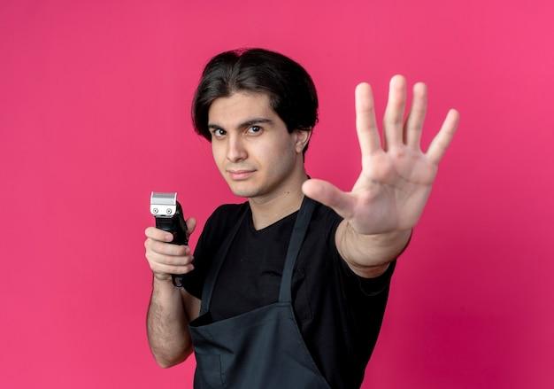Młody przystojny mężczyzna fryzjer w mundurze trzymając maszynkę do strzyżenia włosów i wyciągając rękę na białym tle na różowej ścianie