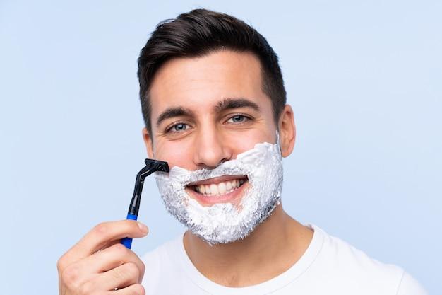 Młody przystojny mężczyzna goli brodę nad odosobnioną ścianą