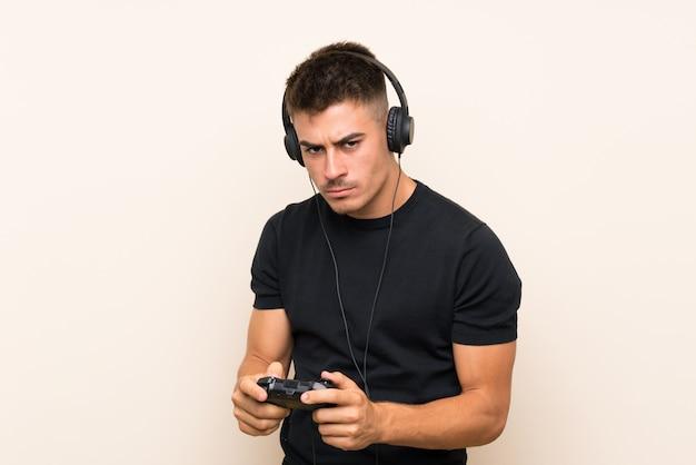 Młody przystojny mężczyzna gra z kontrolerem gier wideo