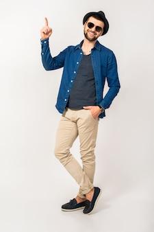 Młody przystojny mężczyzna hipster, modny styl strój, koszula dżinsowa, spodnie, okulary przeciwsłoneczne, kapelusz, na białym tle, skoki, wesoły, palec wskazujący