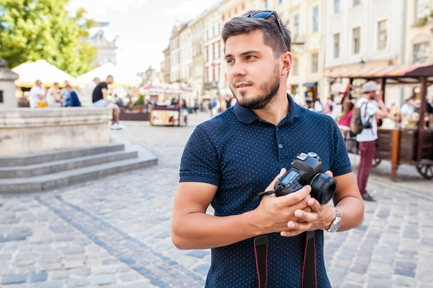 Młody przystojny mężczyzna hipster z aparatu fotograficznego na starej ulicy miasta