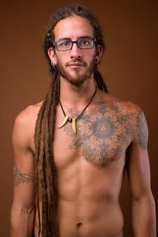 Młody przystojny mężczyzna hiszpanie z dredami bez koszuli przed br