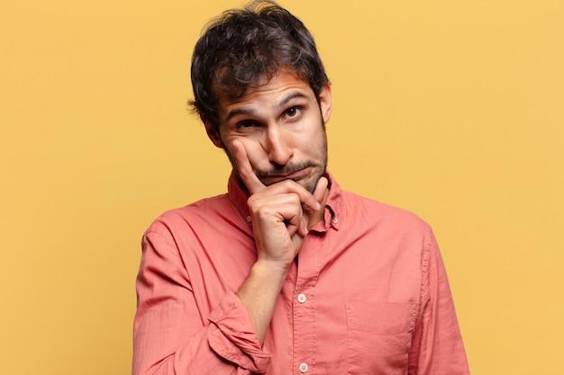 Młody przystojny mężczyzna indyjski. myślenie lub wyrażanie wątpliwości