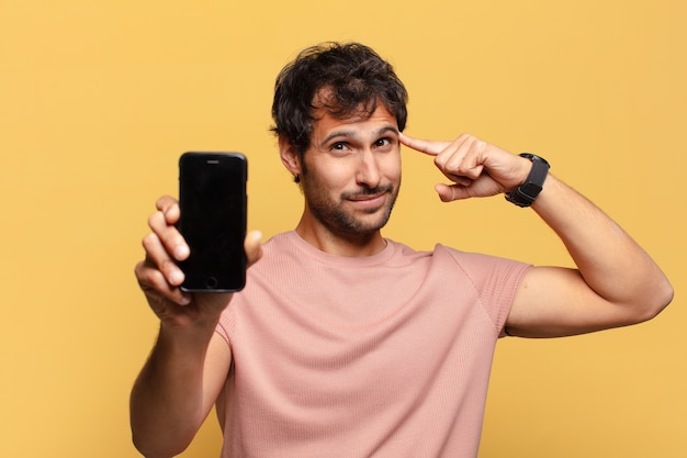 Młody przystojny mężczyzna indyjski myśli koncepcja smartfona