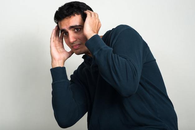 Młody przystojny mężczyzna indyjski na białej ścianie