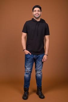 Młody przystojny mężczyzna indyjski na brązowym tle