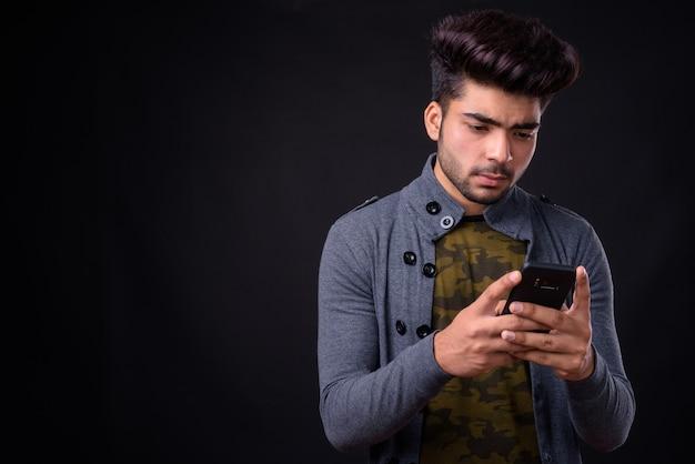 Młody przystojny mężczyzna indyjski na czarnym tle