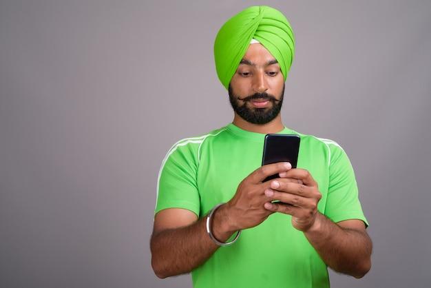 Młody przystojny mężczyzna indyjski sikh sms-y z telefonu komórkowego