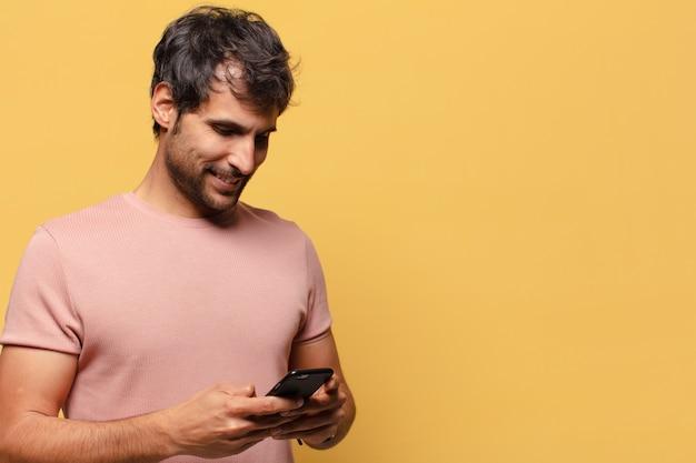 Młody przystojny mężczyzna indyjski. szczęśliwa i zdziwiona koncepcja smartfona ekspresji