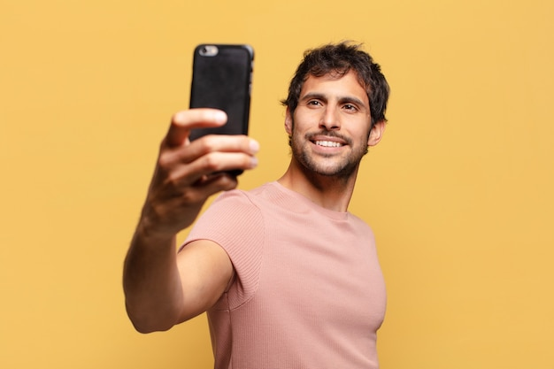 Młody przystojny mężczyzna indyjski. szczęśliwa i zdziwiona koncepcja smartfona ekspresyjnego