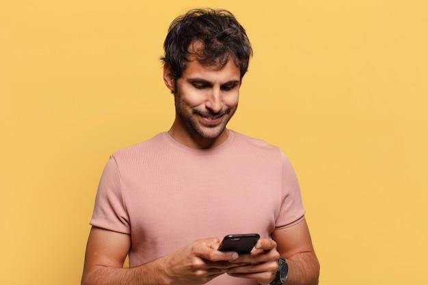 Młody przystojny mężczyzna indyjski. szczęśliwy i zaskoczony koncepcja smartfona z ekspresją