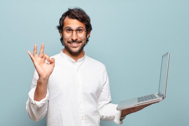 Młody przystojny mężczyzna indyjski trzyma laptopa. koncepcja biznesu lub mediów społecznościowych
