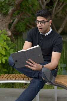Młody przystojny mężczyzna indyjski z okularami, czytanie książki i patrząc w szoku w parku