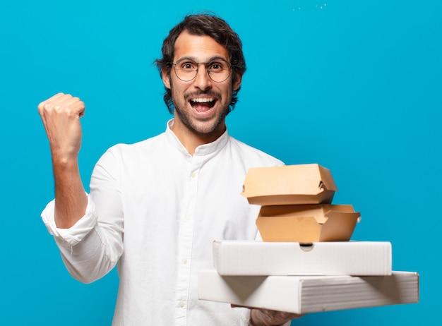 Młody przystojny mężczyzna indyjski zabiera koncepcję fast food