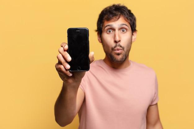 Młody przystojny mężczyzna indyjski. zszokowana lub zdziwiona koncepcja smartfona ekspresji