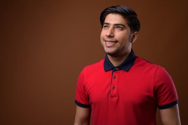 Młody przystojny mężczyzna iranu przed brązową ścianą