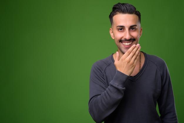 Młody przystojny mężczyzna iranu z wąsem na zielono