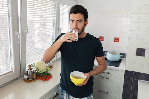 Młody przystojny mężczyzna je śniadanie w kuchni w domu. na śniadanie facet przygotował płatki owsiane i szklankę mleka.