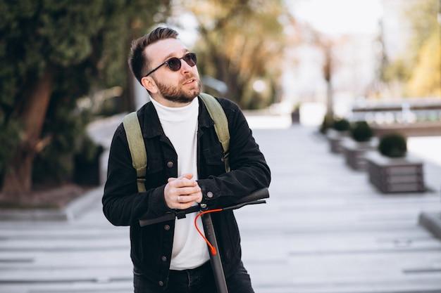 Młody przystojny mężczyzna jedzie na hulajnoga w parku