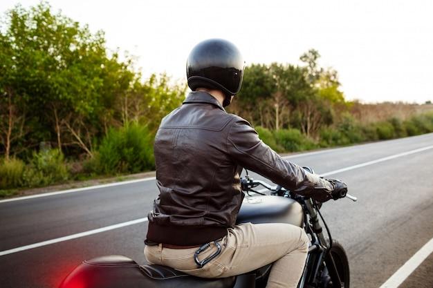 Młody przystojny mężczyzna jedzie na motocyklu przy wsi drogą.