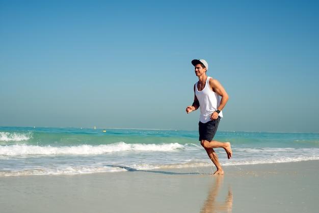 Młody przystojny mężczyzna jest ubranym nakrętkę podczas gdy biegający na plaży.