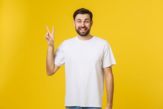 Młody przystojny mężczyzna jest ubranym pasiastą koszulkę nad odosobnionym żółtym ono uśmiecha się patrzeć kamera