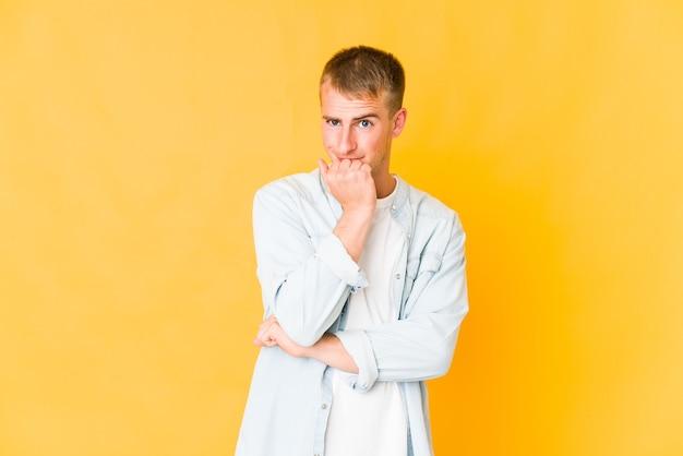 Młody przystojny mężczyzna kaukaski gryzie paznokcie, jest zdenerwowany i bardzo niespokojny.