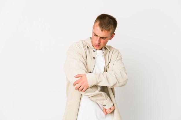 Młody przystojny mężczyzna kaukaski masuje łokieć, cierpi po złym ruchu.