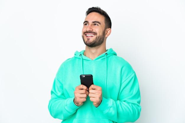 Młody przystojny mężczyzna kaukaski na białym tle na białej ścianie przy użyciu telefonu komórkowego i patrząc w górę
