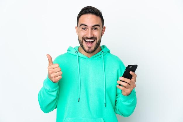 Młody przystojny mężczyzna kaukaski na białym tle na białym tle przy użyciu telefonu komórkowego, robiąc kciuki do góry