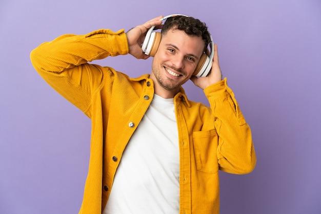 Młody przystojny mężczyzna kaukaski na białym tle na fioletowej ścianie słuchania muzyki