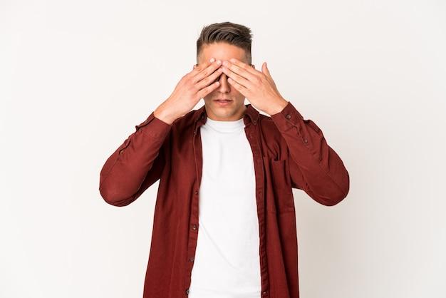 Młody przystojny mężczyzna kaukaski na białym tle przestraszony obejmujące oczy rękami.