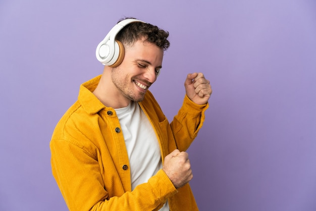 Młody przystojny mężczyzna kaukaski na białym tle słuchania muzyki i tańca