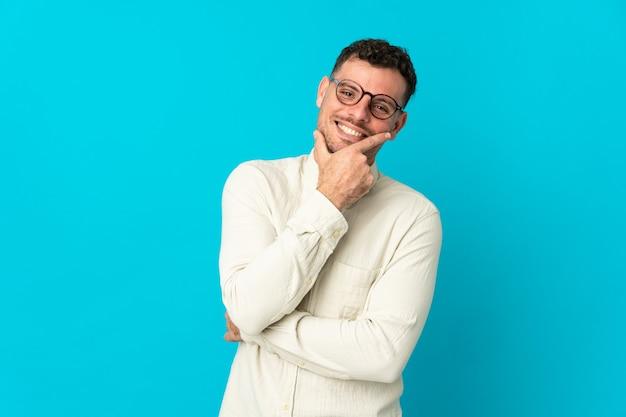Młody przystojny mężczyzna kaukaski na białym tle szczęśliwy i uśmiechnięty